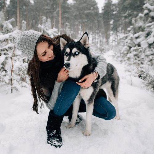 husky and owner in the snow